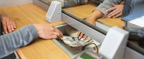 Image of a countertop at a Bank where the banker is passing money underneath the window to a recipient