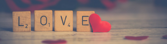 'LOVE' is spelt out with scrabble letters standing up, with a red heart at the end of the 'e'. Red hearts are also flat on the table which are out of focus