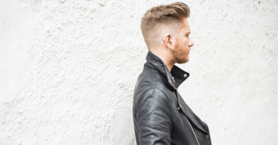 Side portrait of lifestyle blogger Luke Christian who is facing right. Wearing a black leather jacket. Blonde hair styled into a quiff, wearing a small beige hearing aid. Photo against a white textured wall.