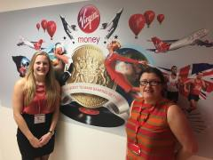 DB standing to left, and Vick from Virgin Money Bank standing to the right. Between them on the wall is a big mural photo collage with lots of Virgin services and products with their motto 'On a quest to make banking better'