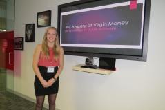 DB standing to the left of a TV screen with her presentation. Main slide is purple and says #ICANuary at Virgin Money, Presentation by Deafie Blogger