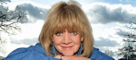 Close up head and shoulders shot of Amanda Barrie wearing a blue denim shirt smiling directly into the camera with a blue and grey sky behind her`