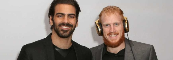 Deaf model Nyle DiMarco and Deaf Twin brother, DJ Nico DiMarco standing next to each other smiling. Nico is wearing headphones