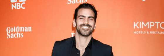 A photo of deaf model Nyle Di Marco smiling, standing against an orange background for an event, wearing a black suit and shirt.