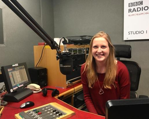 Deafie Blogger smiling sitting in a Radio Recording Studio wearing a red top, heart necklace with recording panels and microphones in front of her