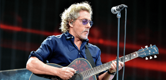 The Who's Roger Daltrey playing guitar on stage with a microphone in front of him. Also wearing protective earpieces