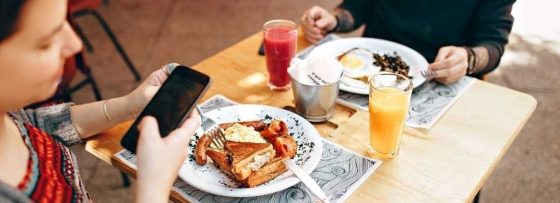 Couple at a small table in a restaurant, camera angle looking down at the table which the girl is holding her phone and there are two plates, both with a fry up on, and one has orange juice, the other has cranberry or tomato juice.