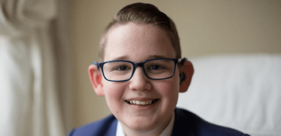 Photo of Reuben Litherland who received an invite to the Royal Wedding. Close up of face, smiling wearing hearing aids and glasses.