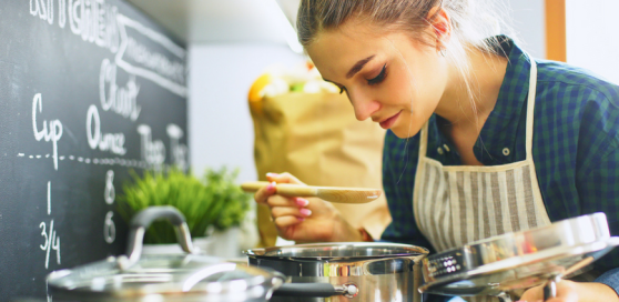 Woman smelling a saucepan on the hob in the kitchen. To her left is another saucepan and also a chalkboard with written measurements on it and also in the background is a green herb plant and next to it is a brown carrier bag but they are blurred