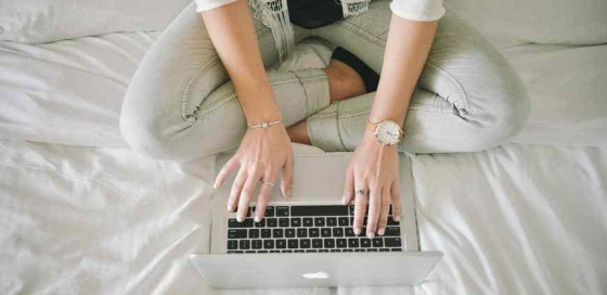 Birds eye view of girl typing on a laptop while sitting on a bed with legs crossed