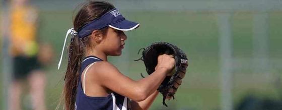 Photo of a young girl with a baseball mitt facing sideways looking straight in that direction. She is wearing a blue and white athletic top and blue and white cap with her hair tied back