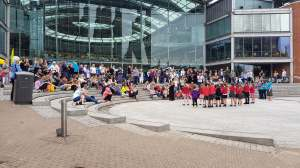 A crowd of people outside the Forum, Norwich watching a School Signing Choir