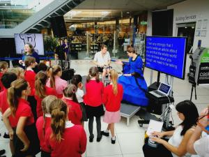 A group of children near the stage watching PAD productions actress dressed up as Harriet Martineau, Deaf Author and her assistant to her left. There is also a lipspeaker on the left side of the stage and a speech to text reporter sitting down on the right side which is projected on a screen what is being said
