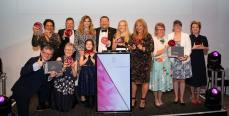 10 Award Winners on the stage smiling with their trophies along with Pip Tomson, I am in the middle next to Craig Crowley MBE in front of a podium.