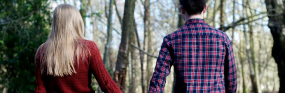 Couple holding hands in the woods, photo taken from behind, girl on left long blonde hair wearing red jumper, boy on right short black hair wearing blue and red chequered shirt