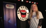 Me smiling wearing white Tshirt with AOHL logo on. In background is comedy store logo and also AOHL banner
