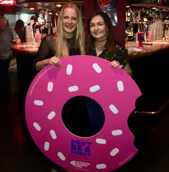 Me and Louise smiling holding a big cutout of a donut