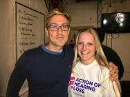 Russell Howard on the left wearing a blue jumper and glasses, on the right is me wearing white AOHL tshirt, both smiling