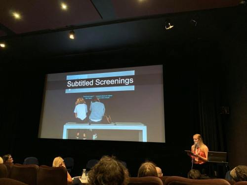 Big screen photo of two girls watching subtitles on a screen. Text says 'Subtitled Screenings'. I can standing at the bottom right giving my presentation.