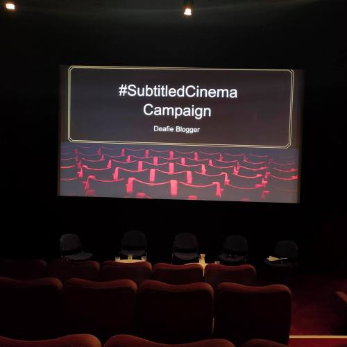 Big screen photo with seats facing big screen and text saying #SubtitledCinema Campaign - Deafie Blogger