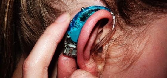 Close up of my turquoise hearing aid with my finger pressing a button