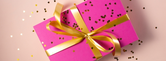 Pink wrapped present with gold ribbon round tied in a bow, covered in confetti