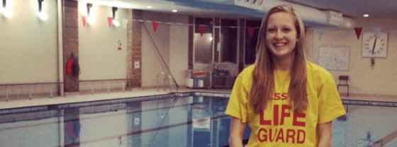 Me, a Deaf Pool Lifeguard in my yellow Lifeguard tshirt standing on poolside with the swimming pool behind me