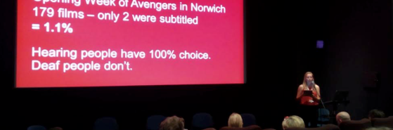 My #SubtitledCinema presentation at the Independent Cinema Office - I am holding a microphone speaking to a crowd, behind me is my powerpoint with stats on