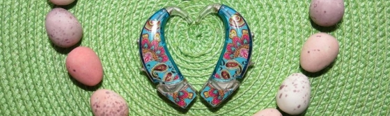 Two turquoise hearing aids in a heart shape. Each hearing aid has a floral patterned sticker on it. Around the heart is some chocolate mini eggs dotted around