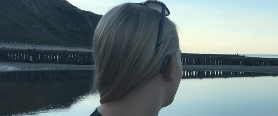 Looking out onto the beach, close up of the back of my hearing aids. I have sunglasses on my head